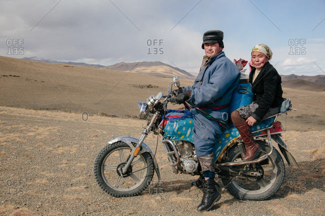 Mongolia - October 10, 2013: Kazakh man and woman on a motorbike in Mongolia