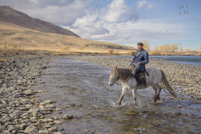 Mongolia - October 10, 2013: A shepherd crosses a shallow river after searching for one of his horses