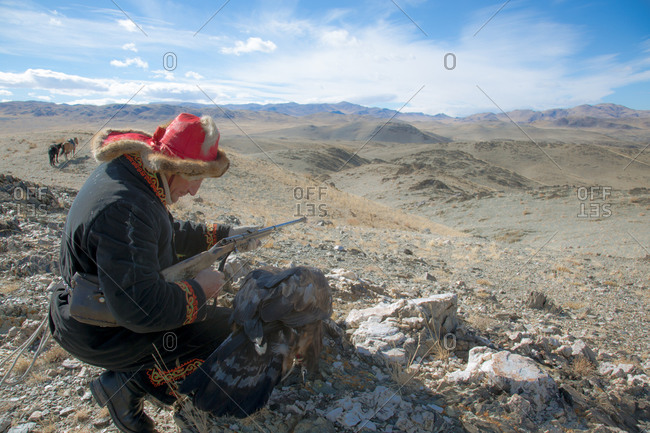 Mongolia - October 11, 2013: Mongolian hunter with his rifle and golden eagle wait on a hillside during a hunt