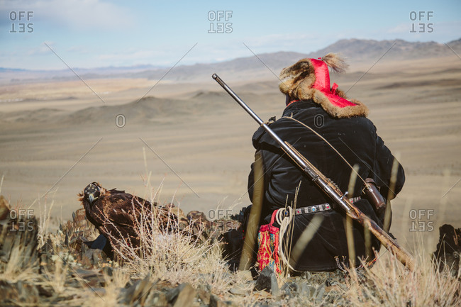 Mongolian hunter and his golden eagle wait on hillside during a hunt