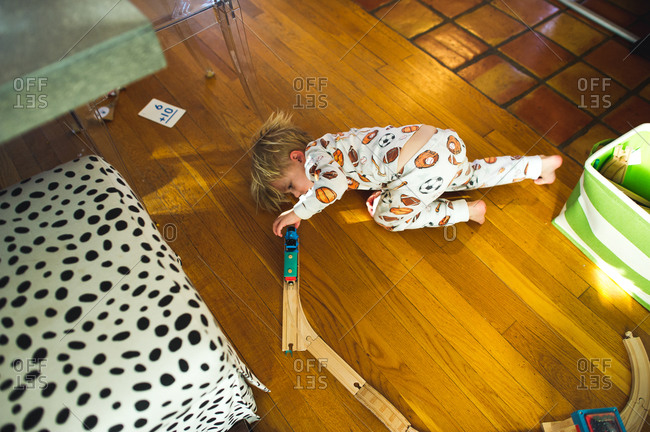 Overhead view of toddler boy lying on floor playing with trains