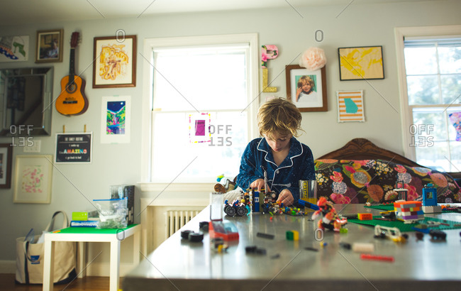 Young boy busy building with toy bricks on table at home