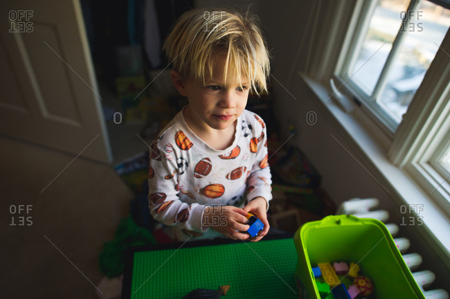Toddler boy in pajamas plays with toy bricks by window