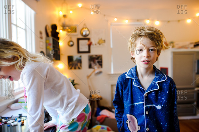 Two young siblings play together in their pajamas in the morning
