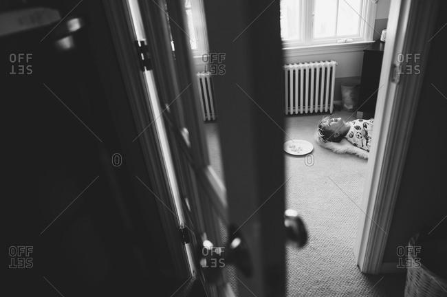 View through doorway of happy child lying on floor with snack