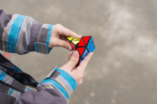 Boy playing with 3-D triangular puzzle