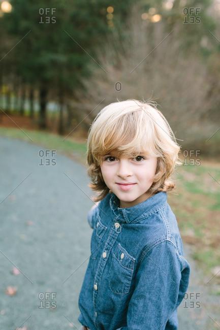 Blonde boy in a denim shirt