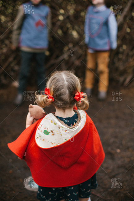 Girl in red cape by boys