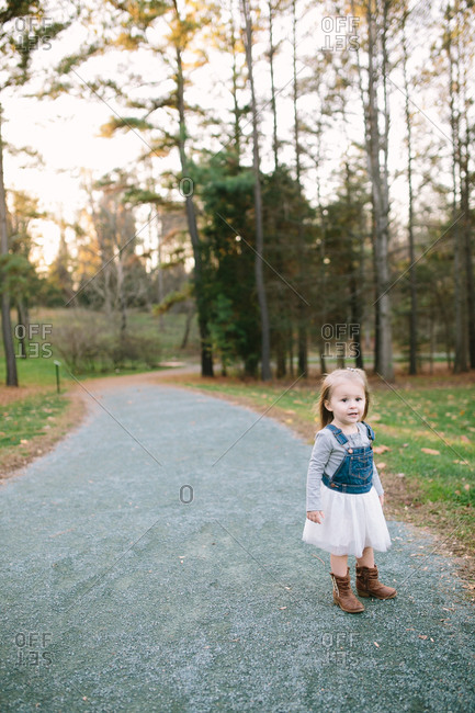 A little girl standing on a path near the woods
