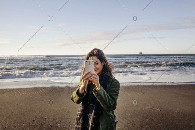 Woman on beach with a smartphone