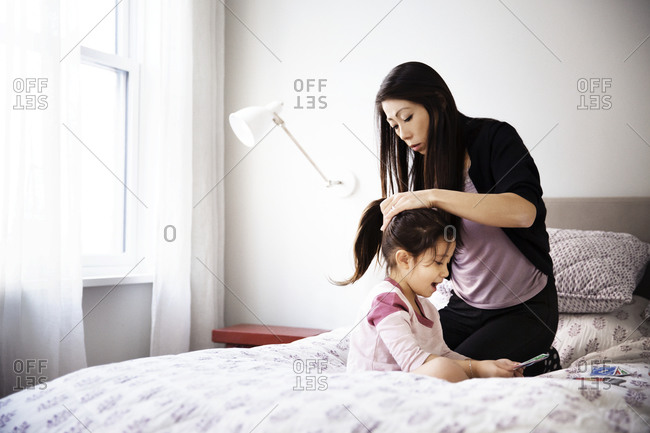 Mom doing girl's hair on bed