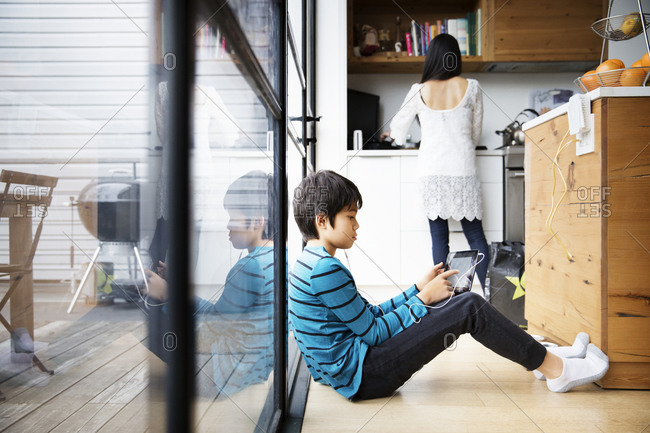 Boy watching tablet, woman in background
