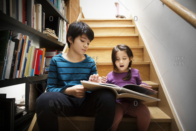 Two kids reading book on stairway
