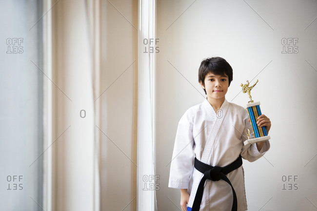 Boy in martial arts outfit with trophy