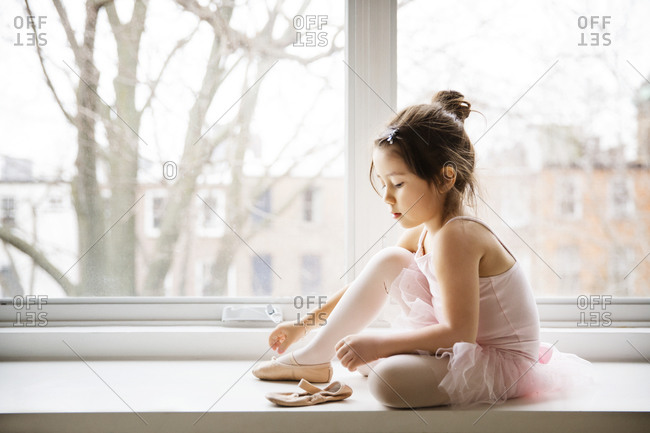 Girl putting on ballet slippers in window