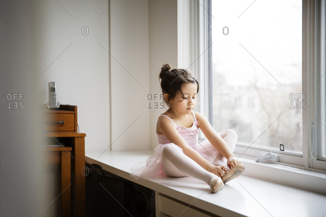 Girl putting on ballet shoes in window