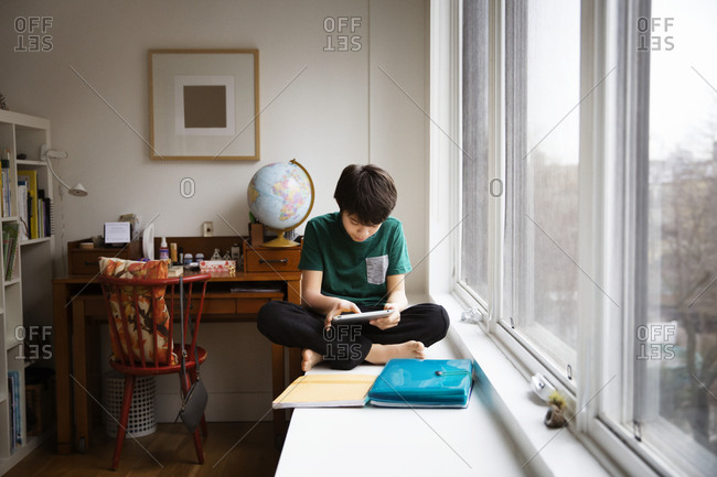 Boy with tablet sitting in window