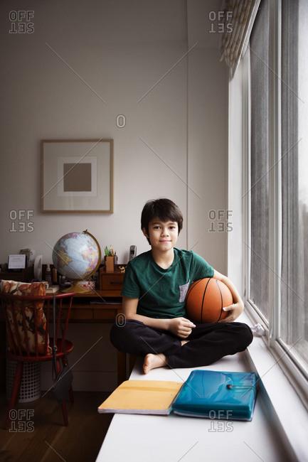 Boy with a basketball on window ledge