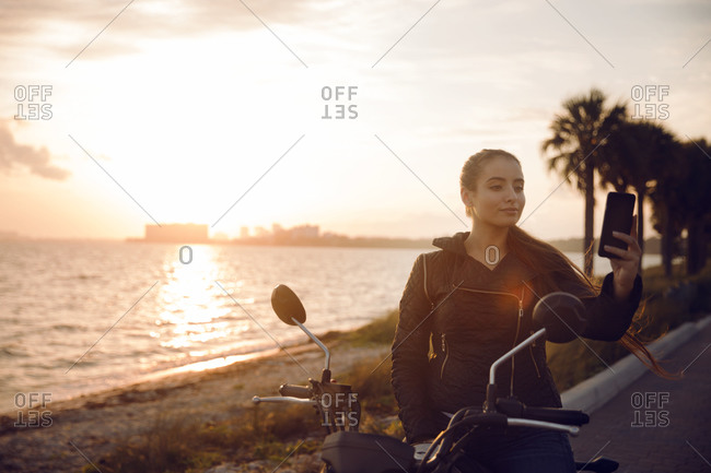 Woman by motorcycle holding smartphone