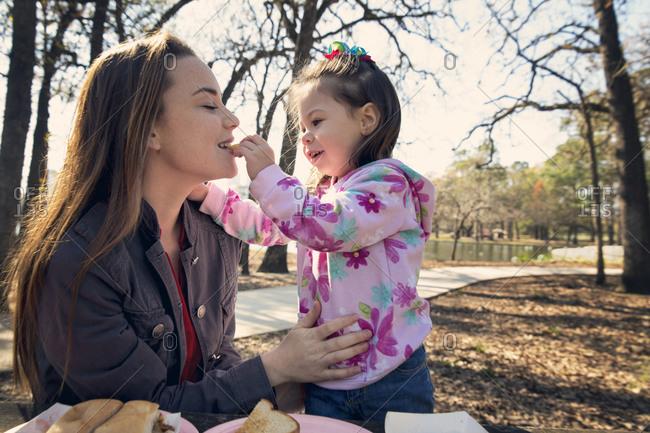 Girl feeding mom at picnic table