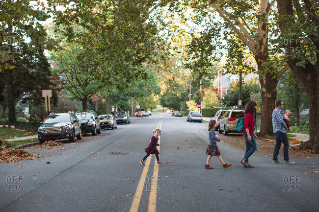Family crossing the street in a leafy suburb