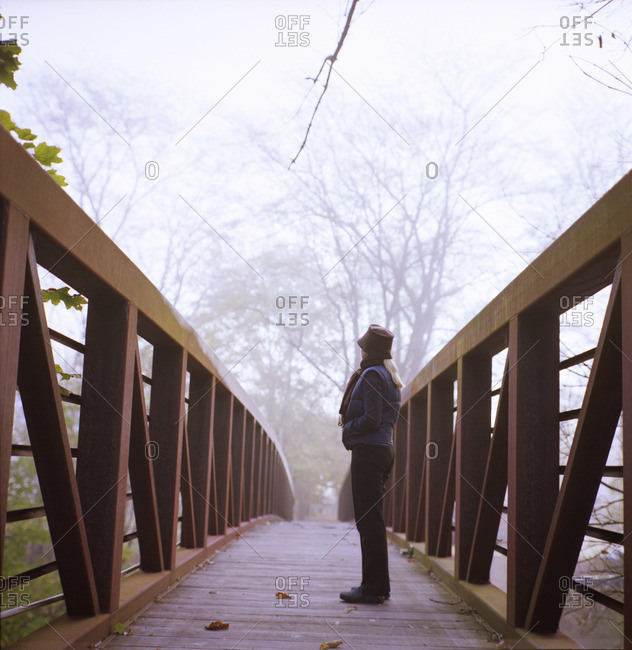 Woman on footbridge in misty countryside