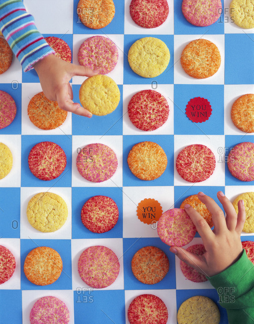 Kids' hands playing game with cookies