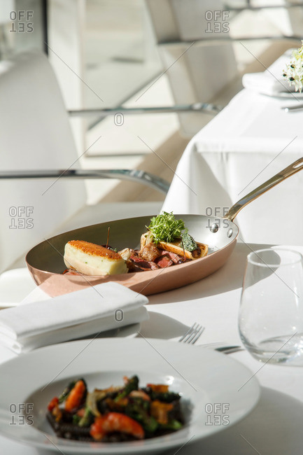 Tables in a restaurant set with stylishly plated entrees