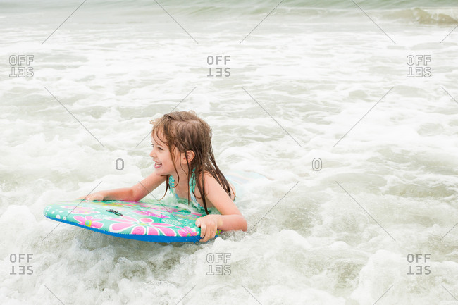 Little girl playing in the water on a kickboard