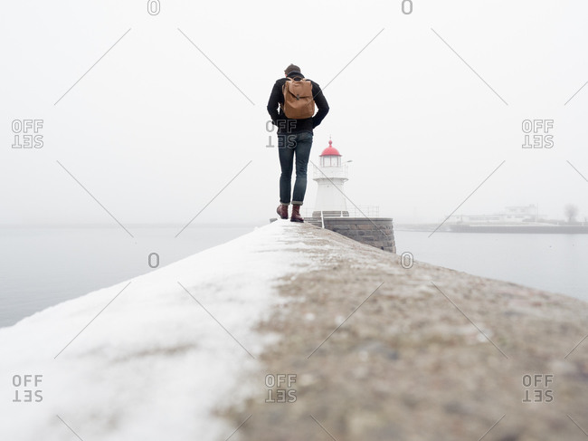 Young man walking on a wall towards a lighthouse