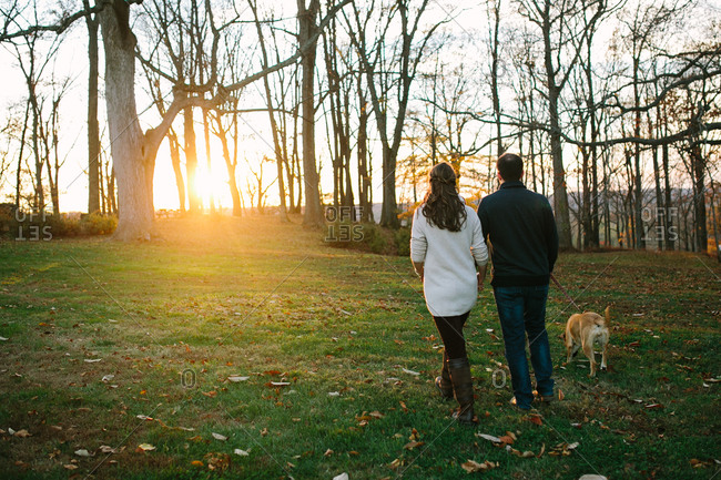 Couple walk their dog in field at dusk