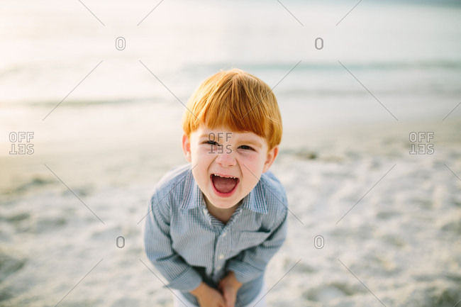 Red haired toddler boy doubled over with laughter