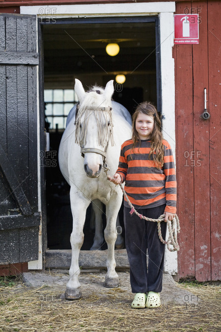 Portrait of girl with horse outside stable