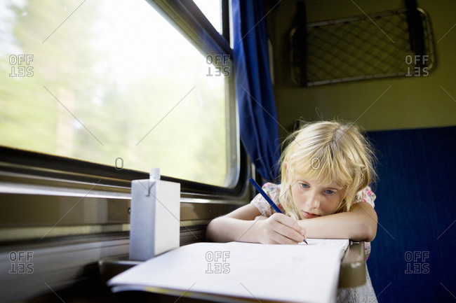Girl drawing in train compartment