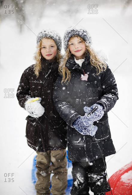 Portrait of identical tween girls in snow