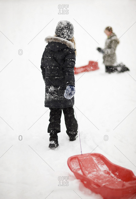 Rear view of girl walking with toboggan in snow