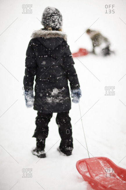 Rear view of girl standing with toboggan in snow