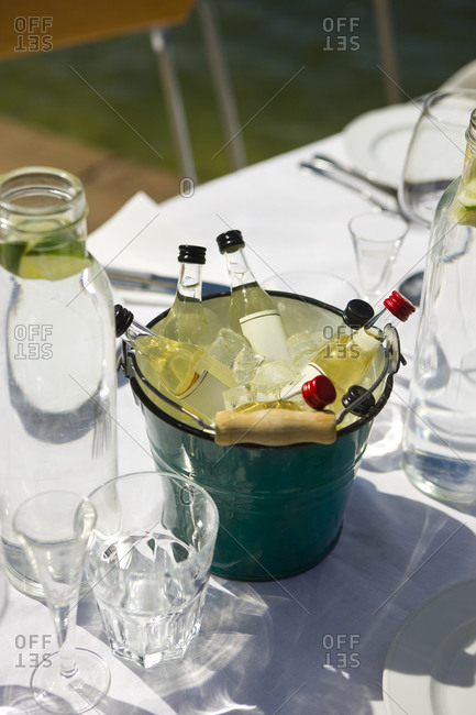 Bottles of liquor in a basket on a table ready laid