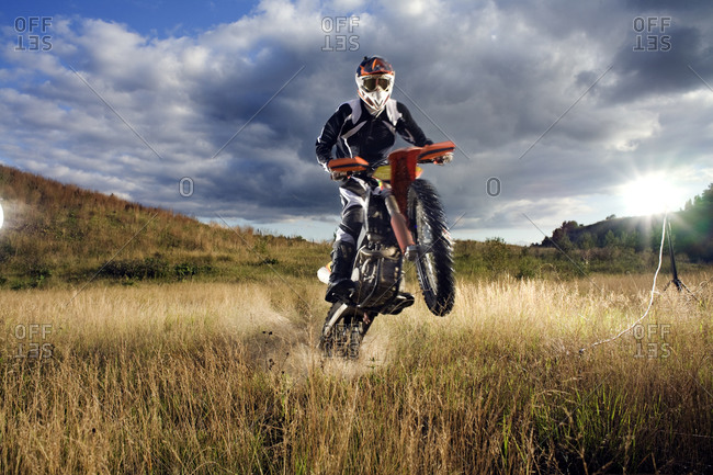 A motocross rider doing tricks in a field