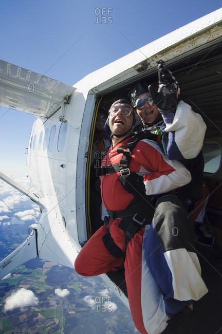A terrified man about to make a parachute jump