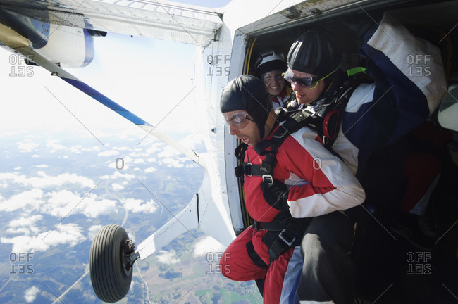 A terrified man about to parachute out of a plane