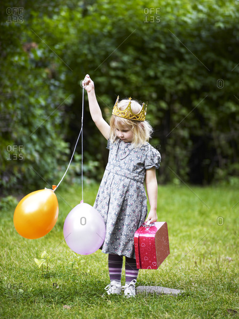 Girl wearing crown standing in park holding balloons and bag