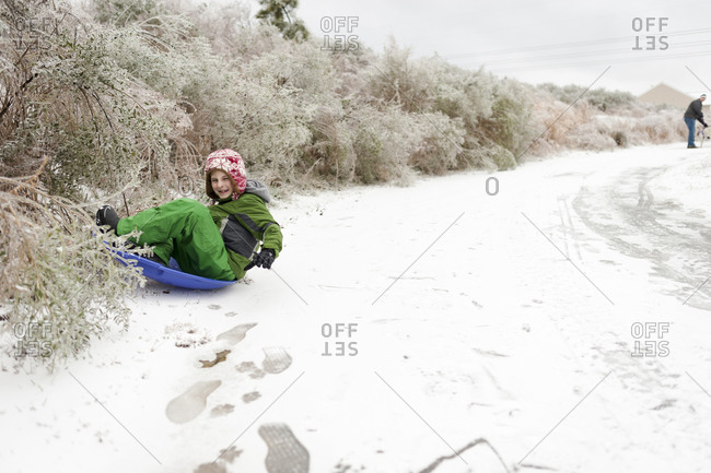 Little boy sledding near bushes on a snowy path
