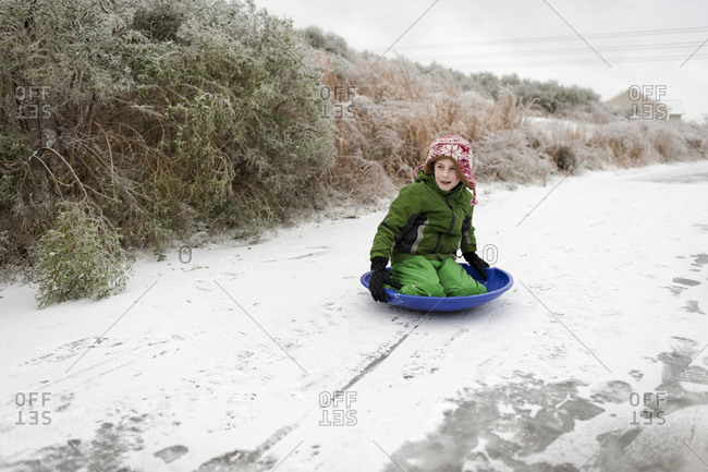 Little boy riding a sled on a snowy path