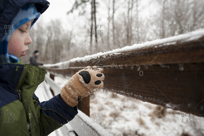 Little boy touching icicles on a wooden railing