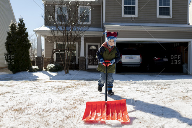 Little boy shoveling snow in a driveway
