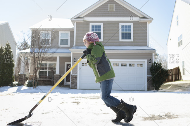 Little boy pushing a shovel through the snow in front of his house