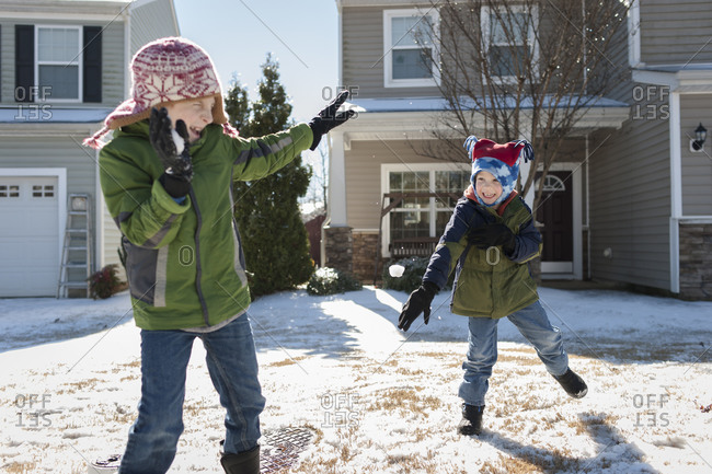 Two brothers throwing snowballs in front of their house