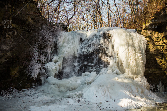 Frozen waterfall cascading over a rocky ledge
