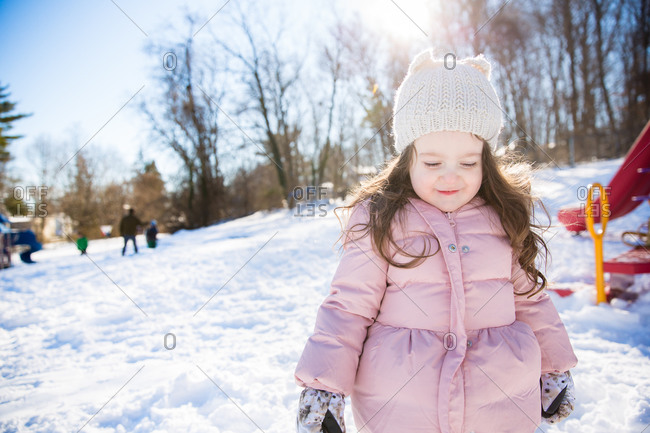 Little girl bundled up and standing in the snow